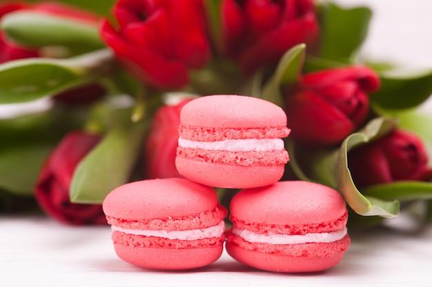 木製の繊細な赤いチューリップとマカロン。閉じる。花の組成。花の春。バレンタインデー、イースター、母の日。