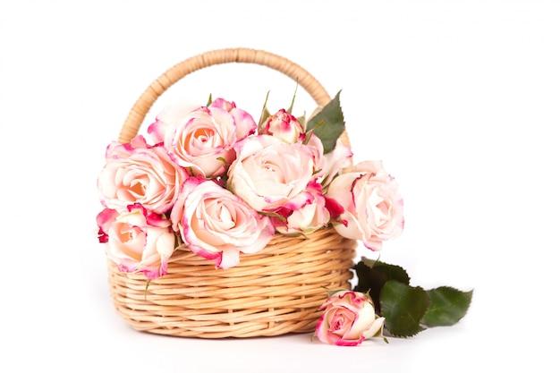 白い背景の枝編み細工品バスケットの美しいピンクのバラ。