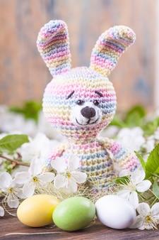 Вязание крючком кролика и пасхальные яйца на фоне нежных цветов вишни.
