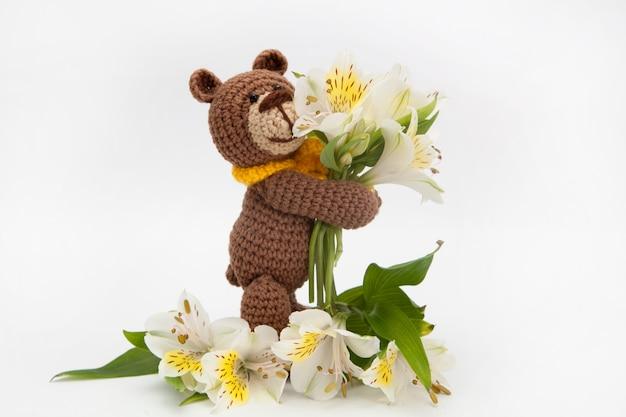 白い花、ニットのおもちゃ、手作りの小さなヒグマ。あみぐるみ。