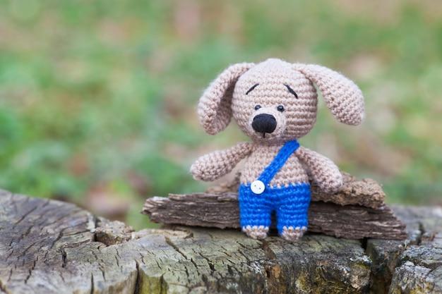 青いズボンの小さな茶色の犬。手作りニットおもちゃ