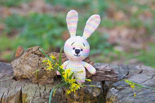 黄色い花を持つ小さなウサギ。手作りニットおもちゃ