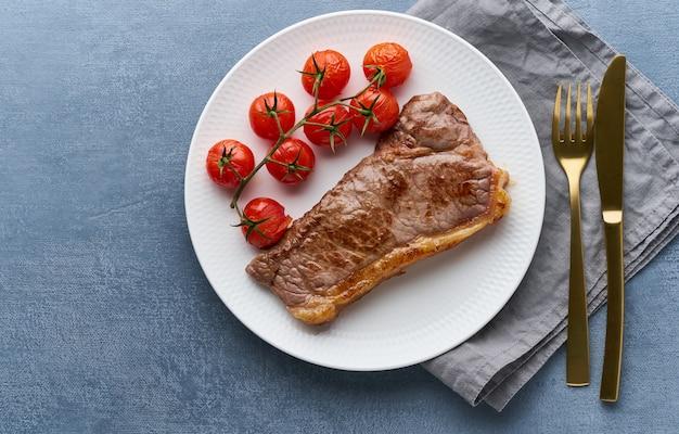 ケトケトジェニックダイエットステーキ、トマトの濃い色の背景に