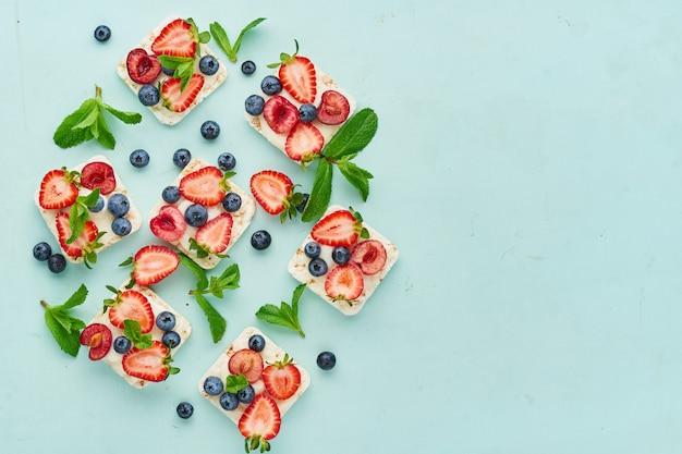 青緑色のアクアマリンの背景に果実や果物のカラフルなコンセプトとクリスプブレッドを上昇