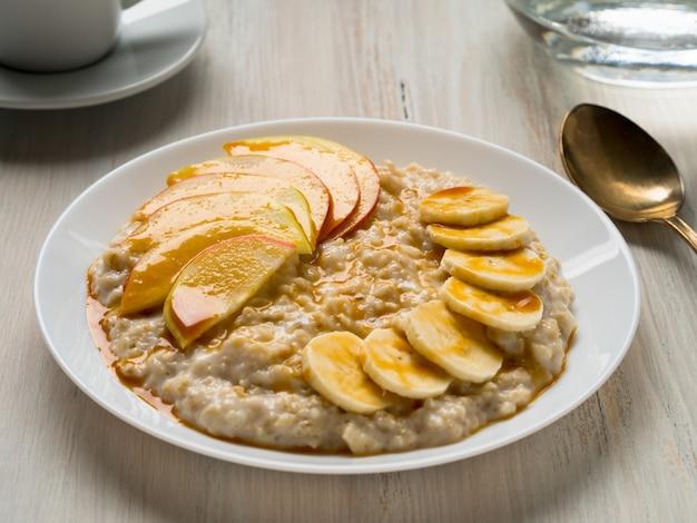 朝の健康的な朝食 - 果物と蜂蜜、リンゴとバナのスライスとオートミール