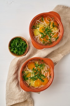 Здоровый куриный суп с овощами и рисовой лапшой, диетическое питание, вид сверху