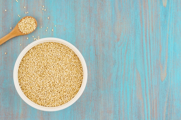 木製のテーブルにスプーンで白いボウルにキノア種子粒