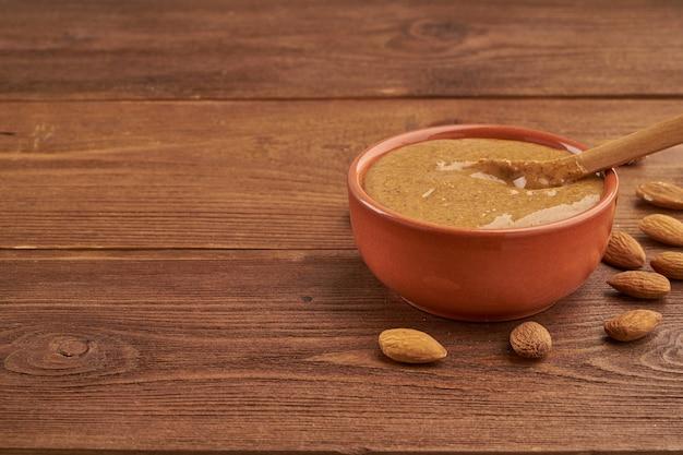 Миндальное масло, сырая пищевая паста, приготовленная из измельченного миндаля в ореховое масло, хрустящее и перемешанное