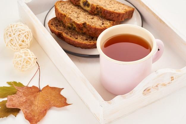 秋のバナナのパンのスライス、お茶、乾燥した葉、白い木製のテーブル。居心地の良い家の冬