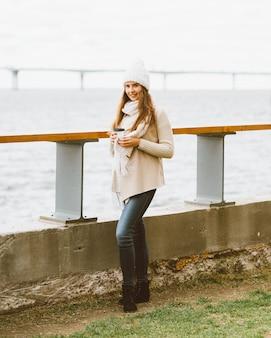長い髪の女性が港とフェリーを待っているバルト海のウォーターフロントに立っています。