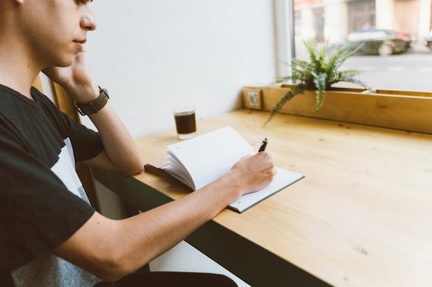 若い男がメモ帳に情報を書いて携帯電話を話す、ティーンエイジャーはスケジュールを計画