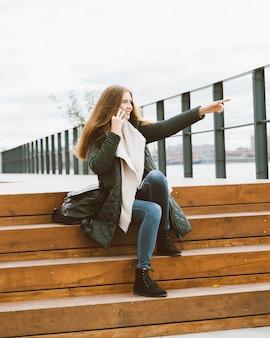 暖かい服装の美しい若い女性は電話で話していると彼女の手で指している