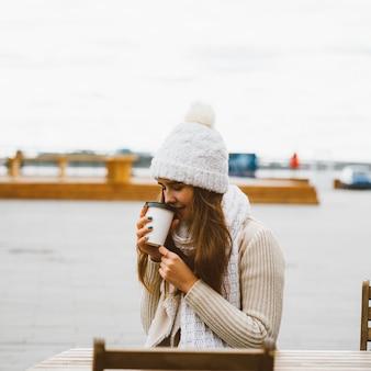 プラスチックマグカップからコーヒーを飲んで美しい少女