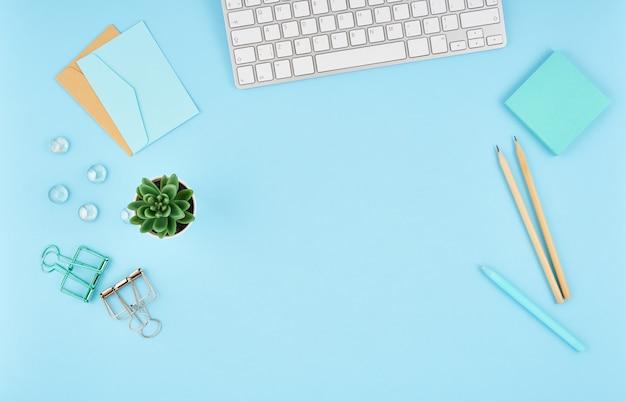 青いオフィスデスクトップ。モダンな明るいテーブル事務用品、キーボードの平面図。