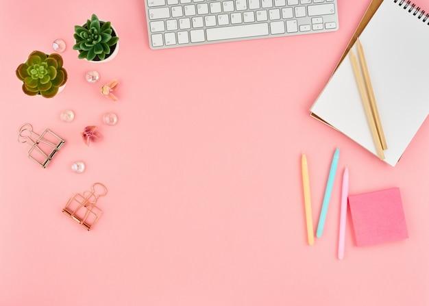 Розовый офисный рабочий стол. взгляд сверху современного яркого блокнота таблицы, клавиатуры. скопировать