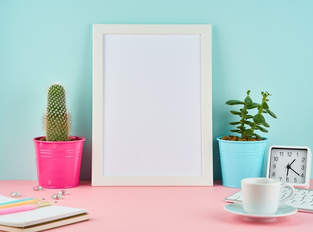 モックアップの空白の白いフレーム、アラーム、メモ帳、コーヒーまたは紅茶のピンクのテーブル