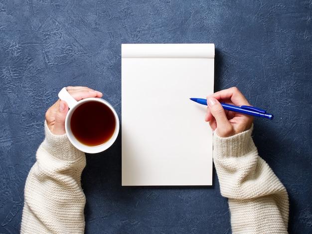 Женщина пишет в тетради на темно-синем столе, рука в рубашке держит карандаш, чашка чая,