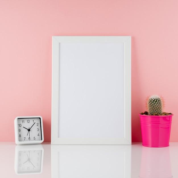 Пустая белая рамка, завод кактусов в розовом горшке на белом столе снова