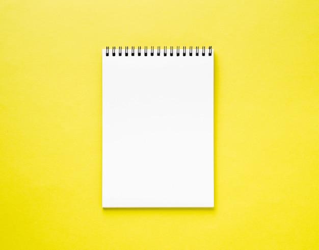Страница пустого блокнота белая на желтом столе, предпосылке цвета. вид сверху, пустой для текста.