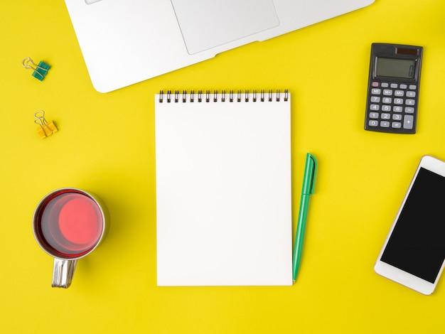 現代の明るい黄色のオフィスデスクトップ空白メモ帳、コンピューター、スマートフォンのトップビュー