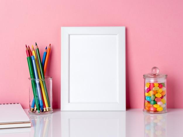 Пустая белая рамка и карандаш в банке, конфеты на белом столе на фоне розовой стене копию