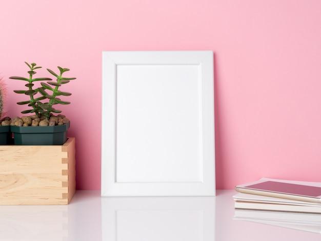 ピンクの壁のコピーに対して白いテーブルに空白の白いフレームと植物サボテン。コピースペースのモックアップ。