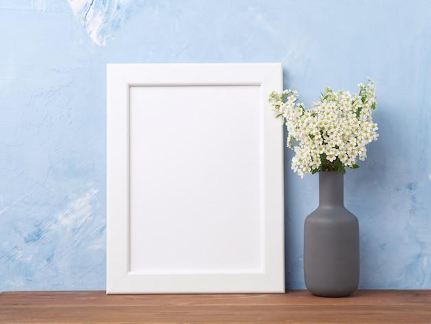 Пустая белая рамка, цветок в вазе на коричневом деревянном столе против пастели