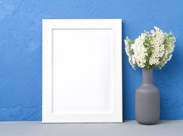Пустая белая рамка, цветок в вазе на сером столе против темно-синей бетонной стены