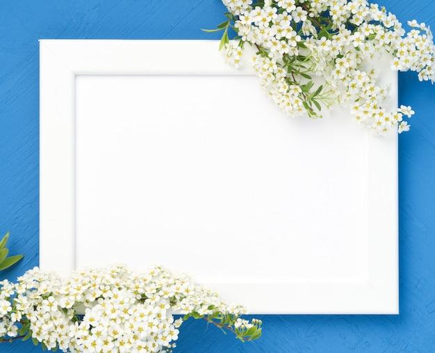 暗い青いコンクリート背景のフレーム上の白い花。背景コピースペース