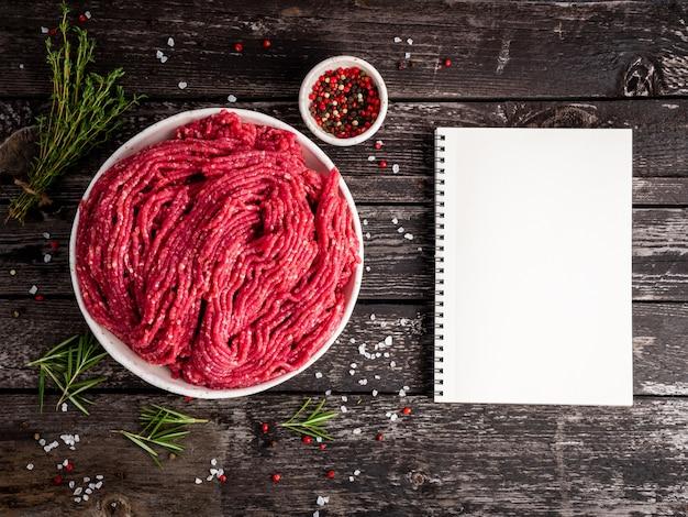 牛肉のミンチ、古い灰色の暗い木製の素朴なテーブルで調理するためのひき肉成分、