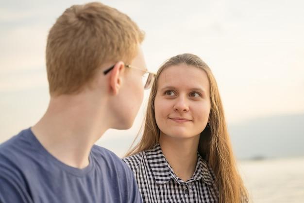 Девушка смотрит на мальчика на пляже на закате, концепция подростковой любви