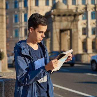 Молодой человек стоит на улице большого города и смотрит на гида, туриста в санкт-петербурге