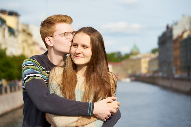 Рыжий мужчина целует женщину в слух, мальчик в свитере утешает девушку с длинными густыми волосами