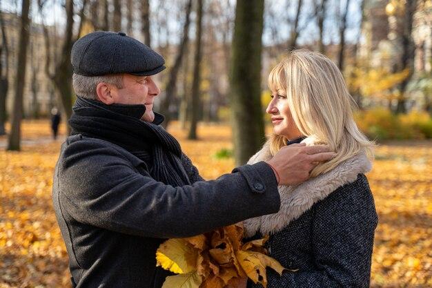 ハンサムなブルネットの中年男は慎重に彼の髪を調整します。幸せな金髪の熟女。