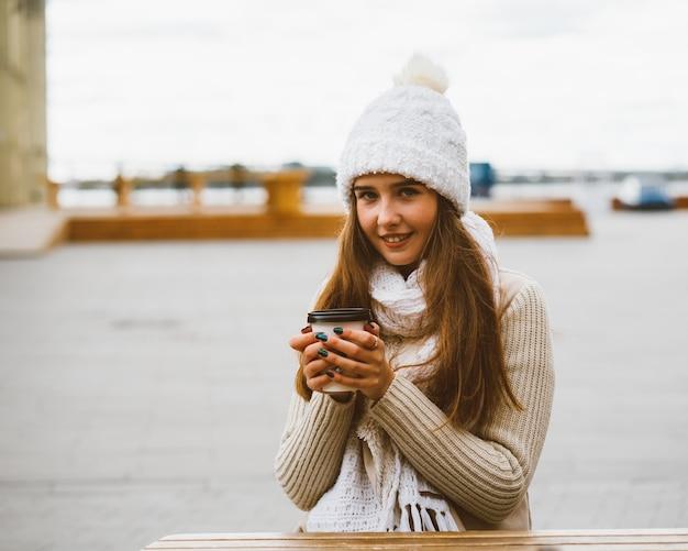 Красивая молодая девушка, глядя на камеру, кофе, чай в пластиковой кружке многоразового использования осенью