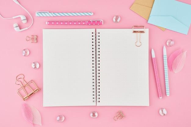 明るいピンクのオフィスのデスクトップ上の弾丸ジャーナルの空白のメモ帳ページ。モダンな明るいテーブルの平面図