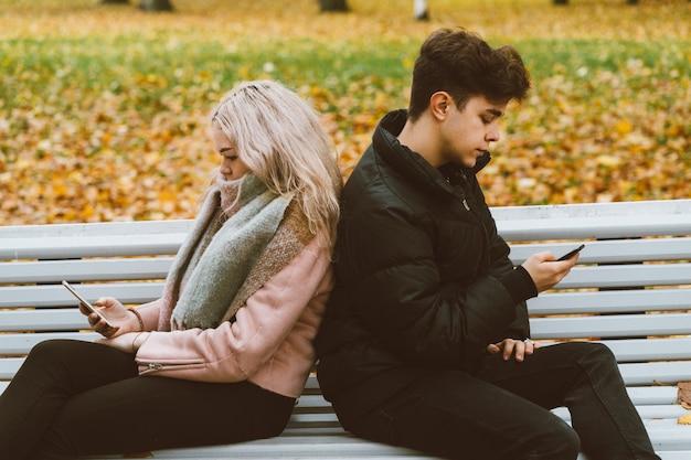 デート中のティーンエイジャーは携帯電話を見て、秋には公園のベンチに座ります。