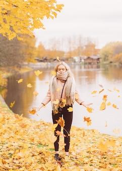 Красивая молодая девушка подбрасывает осенние листья. привлекательная молодая женщина отдыхает, дурачится