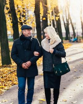 幸せな金髪熟女とハンサムな中年ブルネット男が公園を散歩
