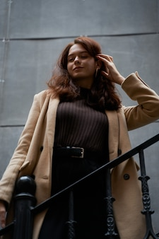 Красивая серьезная стильная модная умная девушка, стоя на лестнице
