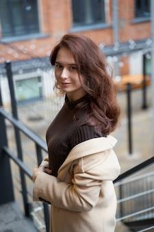 Красивая серьезная стильная модная умная девушка стоит на лестнице и улыбается,