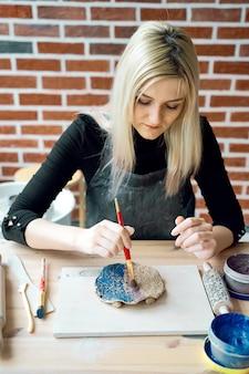 ペイントブラシでセラミックプレートにパターンを作る女性。創造的な趣味のコンセプト。