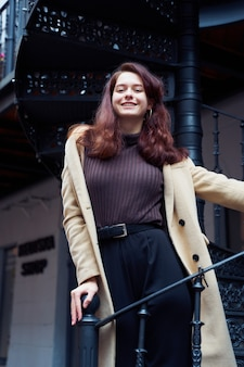 階段の上に立って、笑顔の美しい深刻なスタイリッシュなおしゃれなスマートな女の子