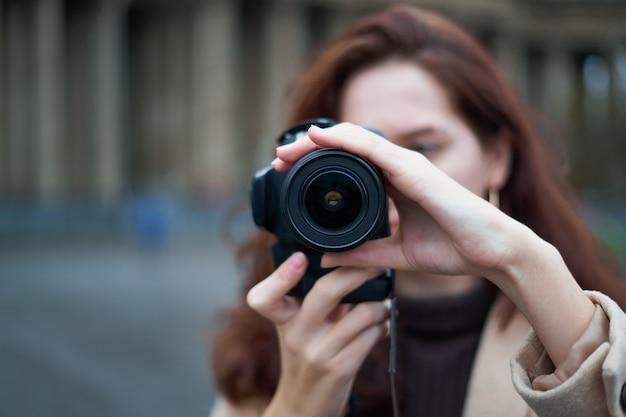 レンズの選択的な焦点。美しいスタイリッシュなファッショナブルな女の子は彼女の手でカメラを保持します