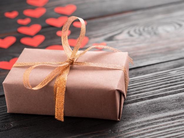 リボンと木のテクスチャ暗い背景、側面に小さな赤いハートがたくさん付いているギフトボックス