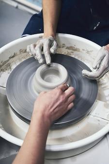 Женщина делает керамическую посуду, четыре руки крупным планом, фокус на гончарах, ладони с глиняной посудой