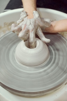 ホイール、手のクローズアップで陶器を作る女性。フリーランスの女性のためのコンセプト