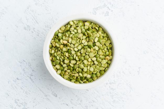 Зеленые горохи в белом шаре на белизне. сушеные хлопья в чашке, веганская еда