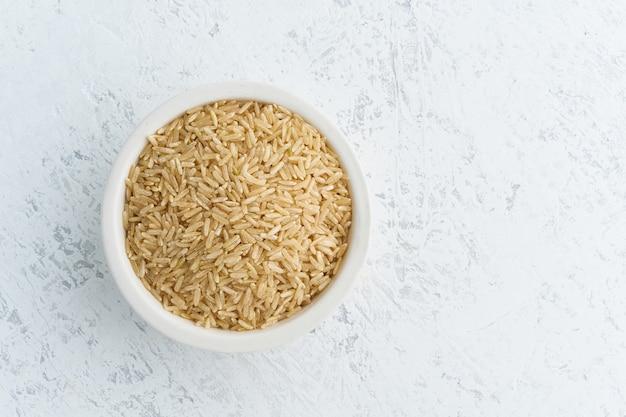 白地に白のボウルに玄米。カップ、ビーガンフードの乾燥シリアル