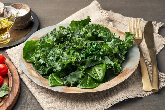 サラダケール、キャベツの葉、コスレタスグリーンのプレートの混合物。